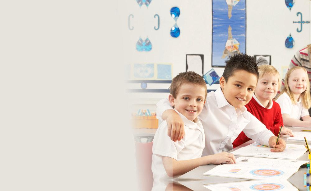 Group of primary school children and teacher working at desks in classroom