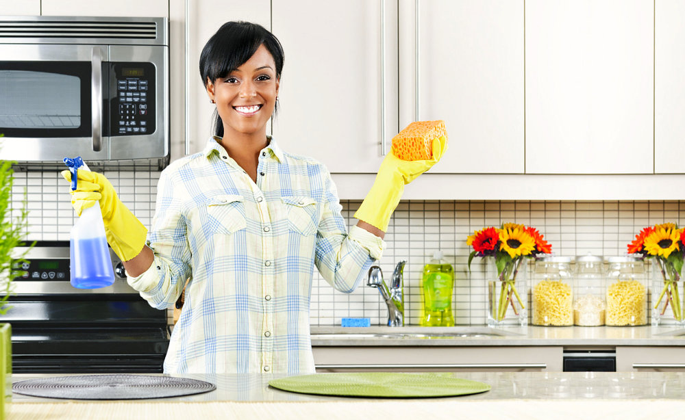 A girl cleaning at the kitchen